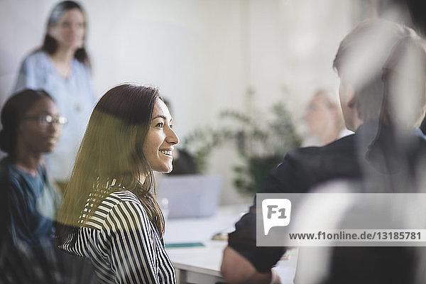 Lächelnde Geschäftsfrau betrachtet Kollegen  der während einer Brainstorming-Sitzung im Kreativbüro erklärt