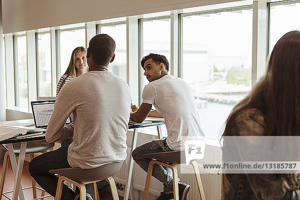 Multi-ethnic university students discussing while studying at cafeteria