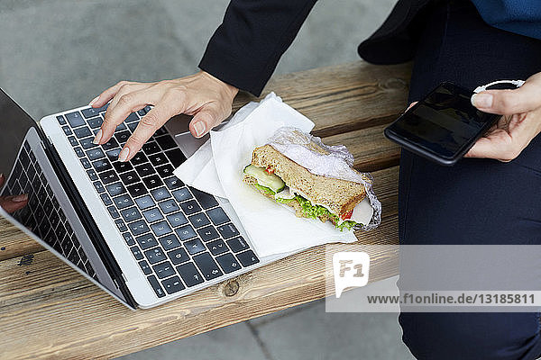 Midsection of businesswoman using laptop while sitting with smart phone and sandwich at bus stop in city