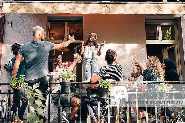 Multi-ethnische Freunde feiern während der Party auf dem Balkon