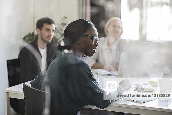 Geschäftsfrau lächelt  während sie während einer Geschäftsbesprechung im Sitzungssaal sitzt