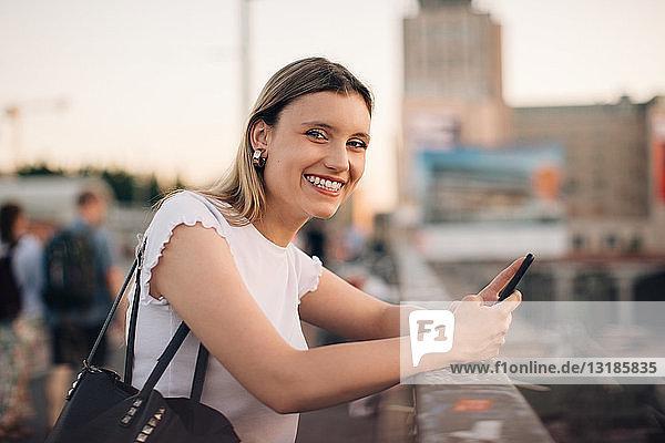 Porträt einer lächelnden jungen Frau  die ein Mobiltelefon in der Hand hält  während sie sich an ein Geländer an einer Brücke in der Stadt lehnt