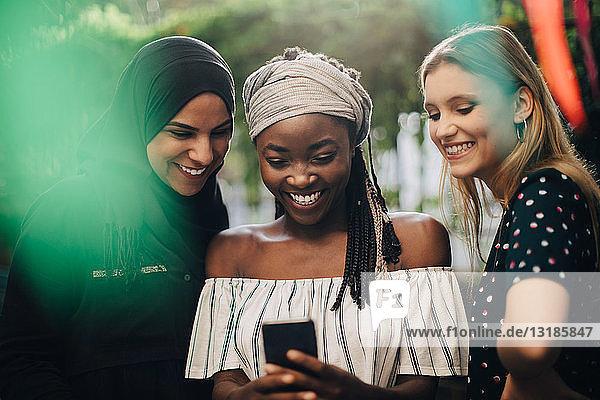 Lächelnde multiethnische Freundinnen  die im Hinterhof stehen und auf ihr Handy schauen
