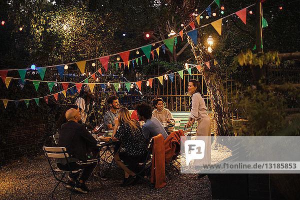Multi-ethnische Freunde und Freundinnen genießen Dinnerparty im beleuchteten Hinterhof