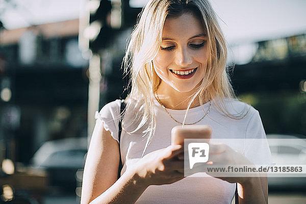 Lächelnde junge Frau benutzt Mobiltelefon  während sie in der Stadt auf der Straße steht