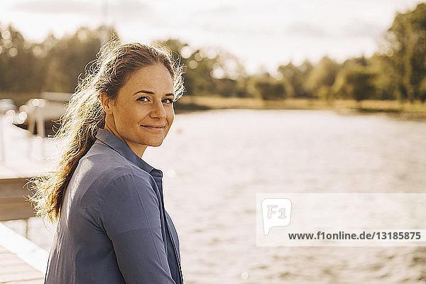 Porträt einer lächelnden  mittelgroßen erwachsenen Frau am See während eines sonnigen Tages