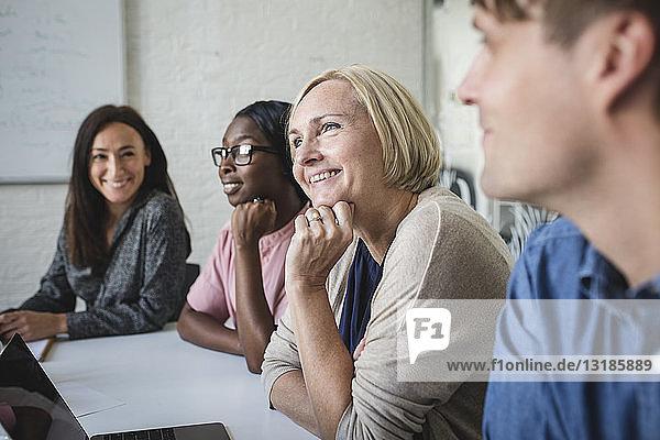 Lächelnde multiethnische Geschäftsleute  die während einer Besprechung im Konferenzraum zuhören