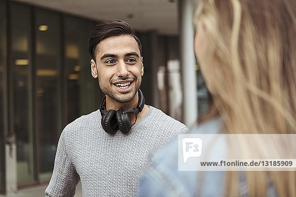 Lächelnder junger Mann im Gespräch mit Freundin auf dem Universitätscampus