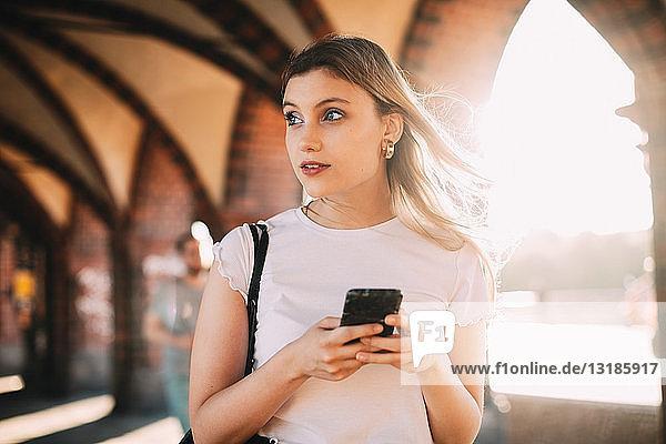 Junge Frau schaut weg  während sie auf einem Fußweg in der Stadt ein Smartphone in der Hand hält