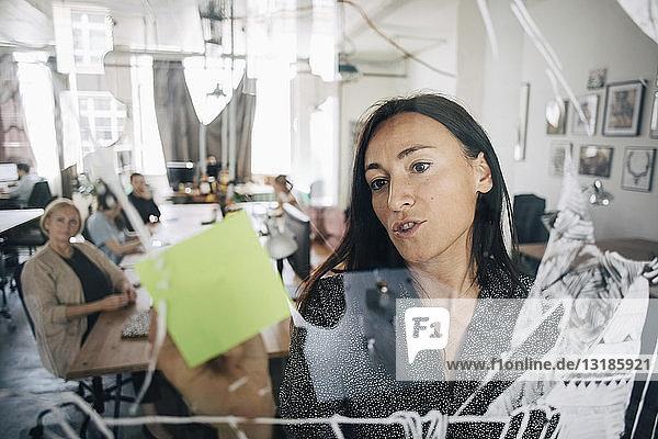 Geschäftsfrau schreibt auf Klebezettel und erklärt Kollegen während einer Besprechung im Kreativbüro