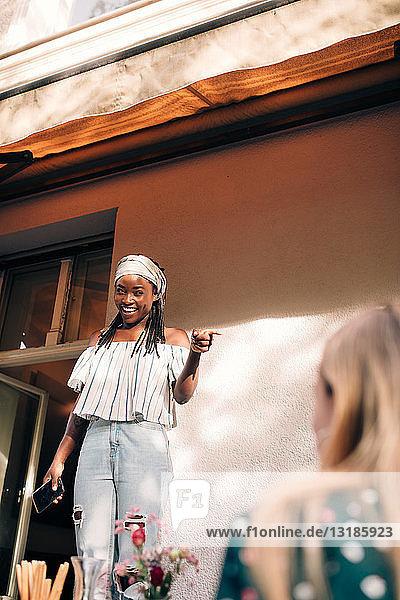 Lächelnde junge Frau zeigt auf Balkon stehend
