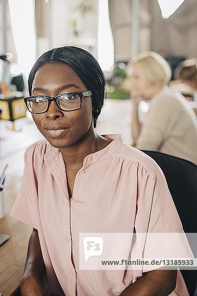 Porträt einer selbstbewussten jungen Geschäftsfrau  die auf einem Stuhl in einem kreativen Büro sitzt