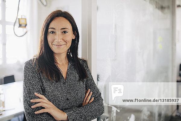 Selbstbewusste kreative Geschäftsfrau steht mit verschränkten Armen im Amt