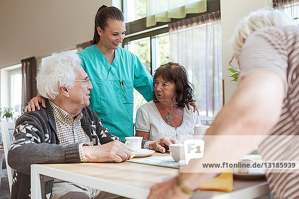 Smiling nurse listening to conversation of senior couple during breakfast at nursing home
