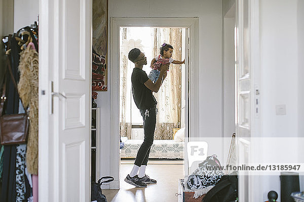 Side view of young man lifting daughter while standing at doorway in house