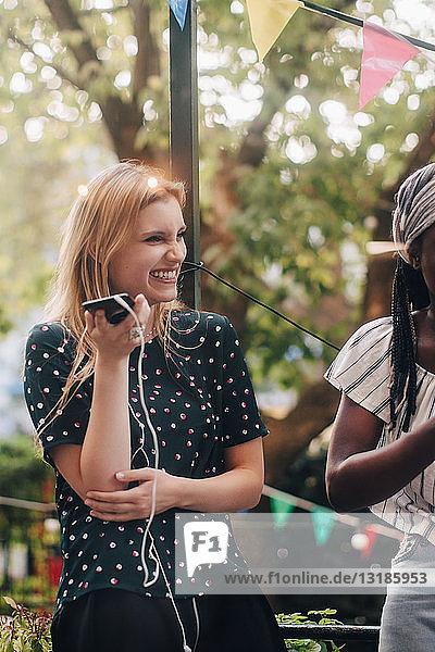 Lächelnde junge Frau hält Handy in der Hand  während sie während der Party bei einer Freundin auf dem Balkon steht