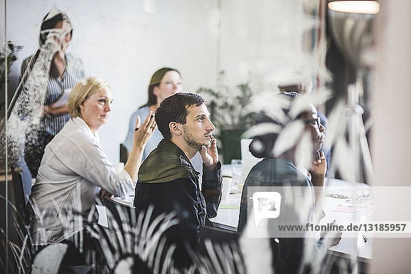 Kreative Geschäftsleute hören zu  während sie im Konferenzraum sitzen
