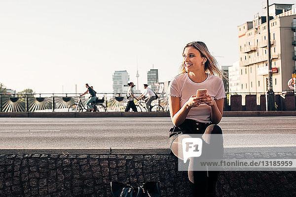 Lächelnde junge Frau hält Handy in der Hand  während sie auf einer Stützmauer an der Straße sitzt
