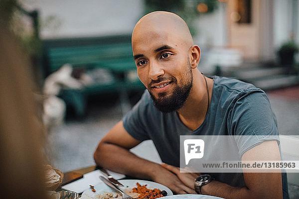 Lächelnder junger Mann mit rasiertem Kopf  der während einer Dinnerparty im Hinterhof eine Freundin ansieht