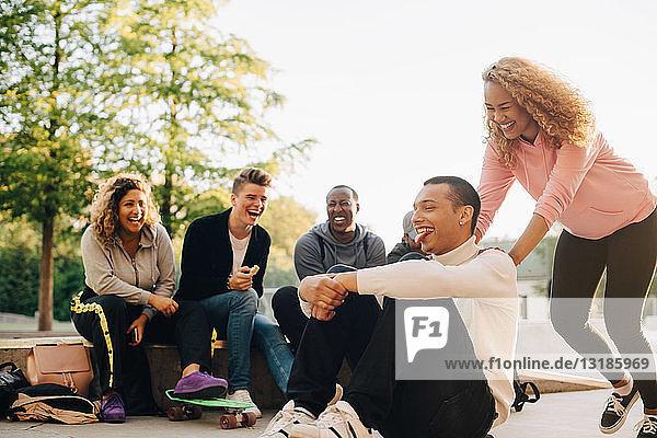 Lächelnde Frau schiebt Mann auf Skateboard  während glückliche Freunde im Park sitzen