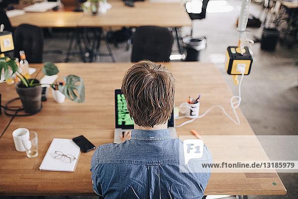 Rückansicht eines Computerprogrammierers  der am Schreibtisch im Kreativbüro arbeitet