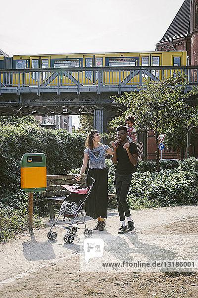 Vater trägt Tochter auf den Schultern  während Mutter Kinderwagen am Fußweg gegen Eisenbahnbrücke schiebt