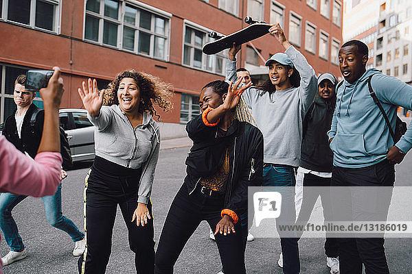 Happy multi-ethnic friends dancing on road in city