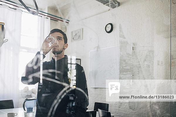 Kreativer Geschäftsmann durch Glas gesehen  während er im Sitzungssaal Wasser trinkt