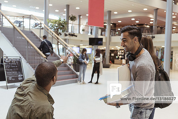 Smiling man looking at student showing direction at corridor in university