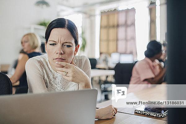 Verwirrte Geschäftsfrau schaut auf den Laptop  während sie im Kreativbüro am Schreibtisch sitzt