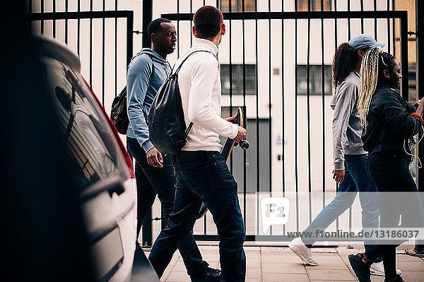 Freunde in voller Länge auf dem Bürgersteig vor dem Tor in der Stadt