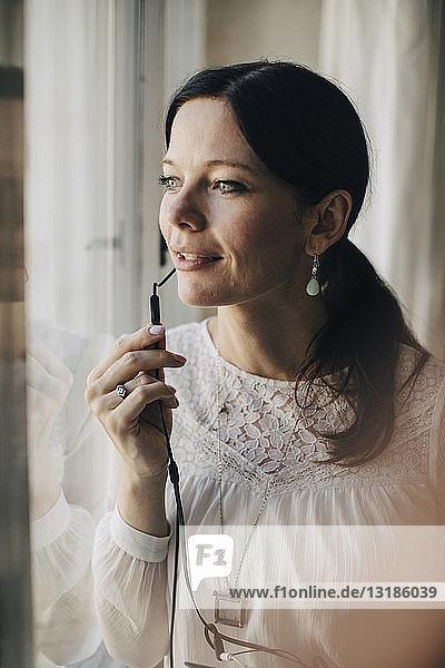 Kreative Geschäftsfrau spricht durch Kopfhörer am Fenster im Büro