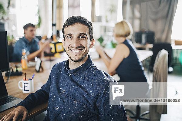 Porträt eines lächelnden jungen Geschäftsmannes  der am Schreibtisch in einem kreativen Büro sitzt