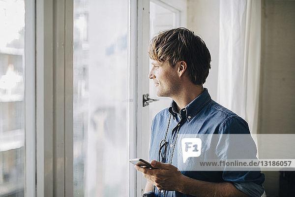 Geschäftsmann schaut durch ein Fenster  während er im kreativen Büro mobil ist