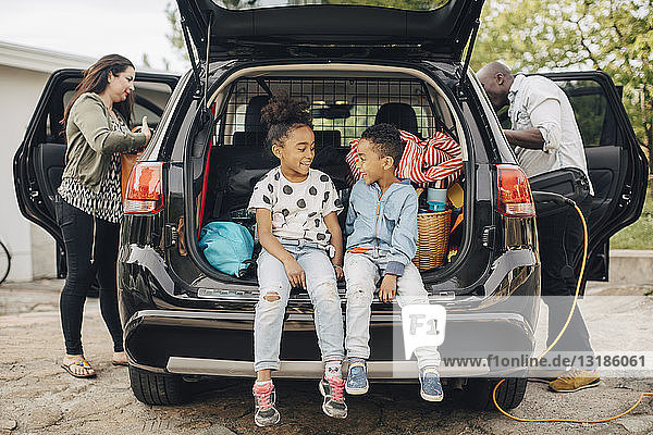 Full length of smiling siblings sitting on car trunk with parents standing in front yard