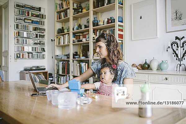 Woman using laptop while sitting with daughter at dining table in house