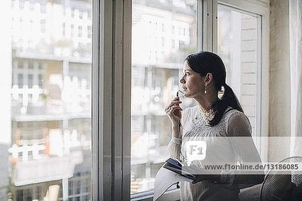 Kreative Geschäftsfrau spricht durch Kopfhörer  während sie im Büro am Fenster steht