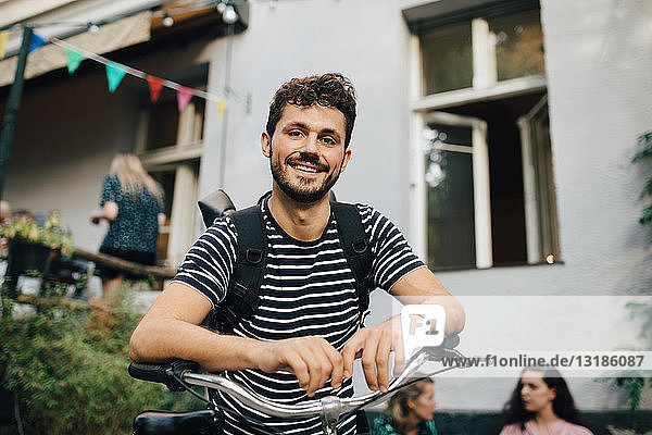 Porträt eines lächelnden jungen Mannes  der sich auf einem Fahrrad im Hinterhof anlehnt