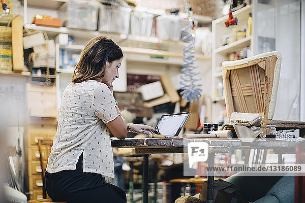 Female upholstery worker using laptop at workbench in workshop
