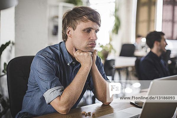 Angespannter Geschäftsmann schaut auf Laptop  während er am Schreibtisch im Kreativbüro sitzt