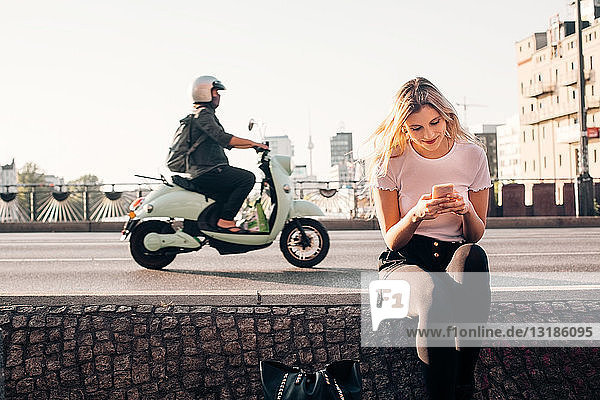 Lächelnde junge Frau  die ein Smartphone benutzt  während sie auf einer Stützmauer an einer Straße in der Stadt sitzt