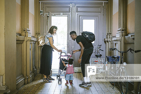 Mutter und Vater sehen Tochter beim Schieben des Kinderwagens im Flur der Wohnung