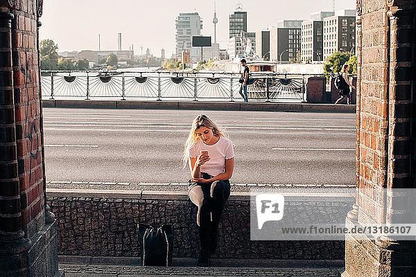 Junge Frau benutzt Mobiltelefon  während sie auf einer Stützmauer an der Straße sitzt
