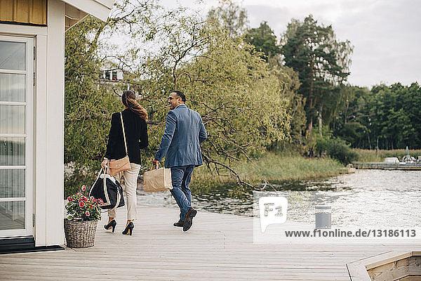 Ausgewachsenes Paar in voller Länge zu Fuß in der Ferienvilla am See