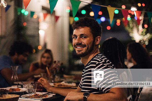 Porträt eines lächelnden jungen Mannes beim Abendessen mit Freunden während einer Gartenparty