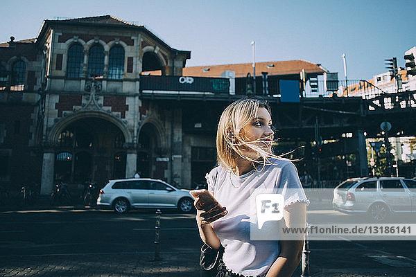 Junge Frau schaut über die Schulter  während sie ein Mobiltelefon auf der Straße in der Stadt hält