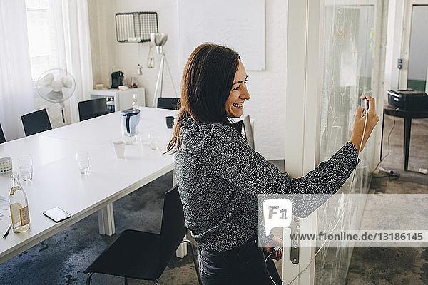 Lächelnde  kreative Geschäftsfrau  die sich beim Stehen an der Tür des Sitzungssaals Selbsthilfe nimmt
