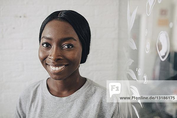Porträt einer selbstbewussten kreativen Geschäftsfrau im Büro an der Wand