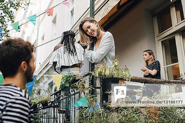Lächelnde junge Frau schaut einen männlichen Freund an  während sie während einer Gartenparty auf dem Balkon steht