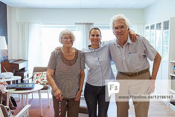 Porträt einer lächelnden jungen Frau mit Großeltern  die zusammen in einem Pflegeheim stehen